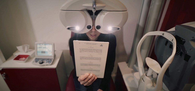 Une patiente qui lit chez l'Ophtalmologiste